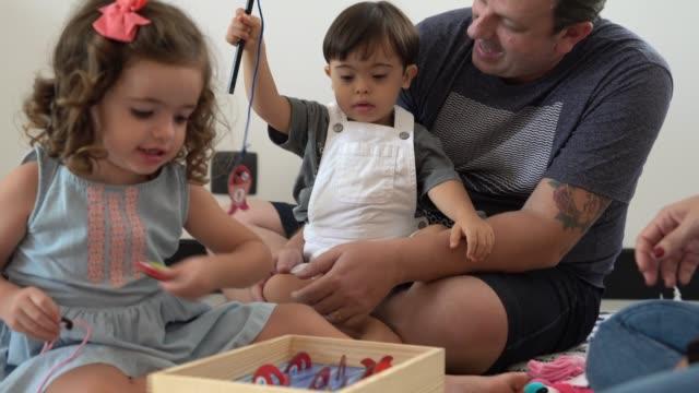 vídeos de stock, filmes e b-roll de família com irmão gêmeo (menino e menina da síndrome de down) que joga com jogos do lazer - criança pequena