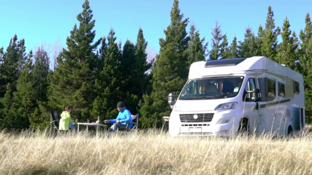 family with two chidren are camping and parking a motorhome beside them in New Zealand video