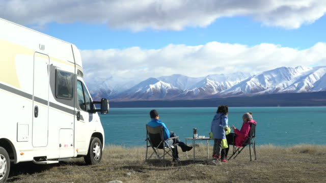 family with two chidren are camping and parking a motorhome beside them in New Zealand 2 video