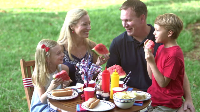 Family with two children at July 4th picnic A family with two children sitting at a table conversing as they eat hot dogs and watermelon. They are celebrating the 4th of July or Memorial Day. The parents are in their 30s, the boy is 9 years old and his sister is 8. family 4th of july videos stock videos & royalty-free footage