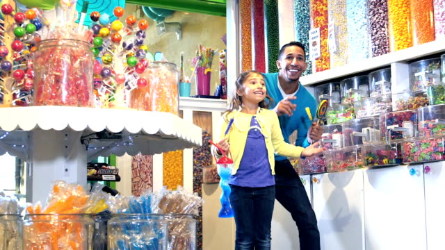 家庭與兩個孩子興奮地在糖果店 - 波板糖 個影片檔及 b 捲影像