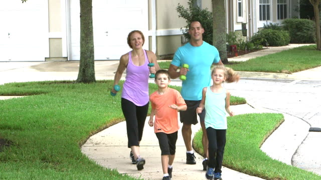 Family with two children exercising together video