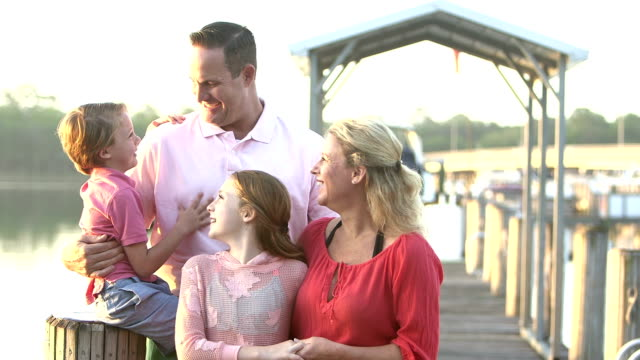 Family with two children standing together on pier