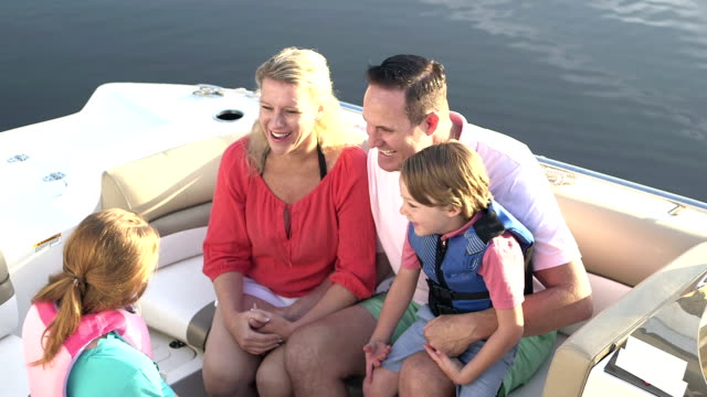 Family with two children taking a boat ride video