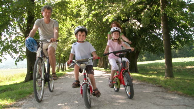 HD: Family With Two Kids Cycling In The Park HD1080p: Camera Stabilization Shot of a family with two kids riding bikes toward a treelined park trail. recreational pursuit stock videos & royalty-free footage