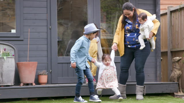A family with young children have fun playing in the garden A family with young children have fun playing in the garden - laughing and smiling life balance stock videos & royalty-free footage