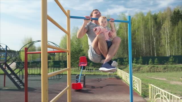vídeos de stock, filmes e b-roll de a família malha. o jovem faz flexões com o bebê. homem adulto realiza exercícios com seu filho pequeno como peso adicional - braço humano