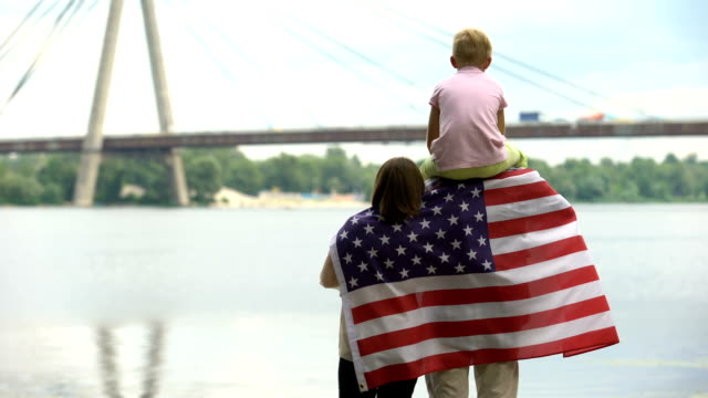 Family wrapped in American flag looking at bridge, immigration, independence day Family wrapped in American flag looking at bridge, immigration, independence day family 4th of july stock videos & royalty-free footage