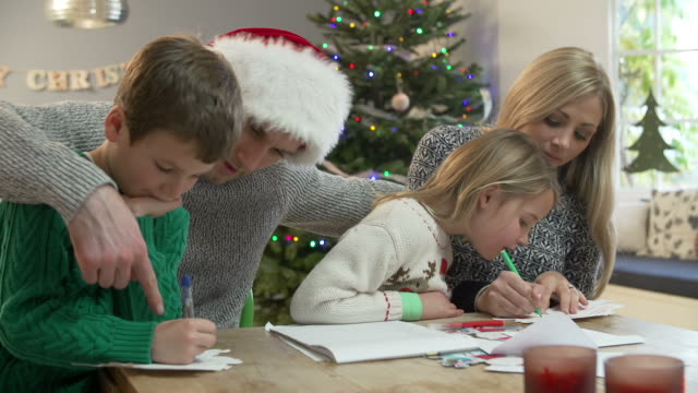 family writing christmas cards together at home - christmas card bildbanksvideor och videomaterial från bakom kulisserna