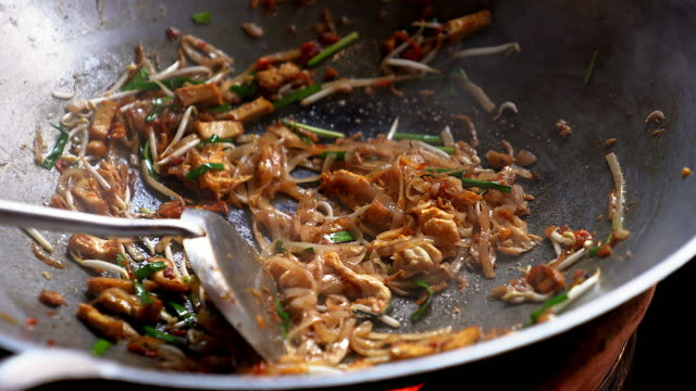 famous asian thai street fast food in a hot pan, pad thai, is a stir-fried rice noodle dish commonly served as a street food and at casual local eateries in thailand. - tajowie filmów i materiałów b-roll