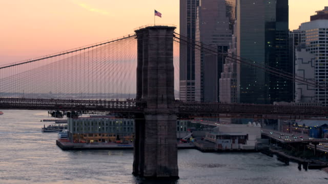 Famous Brooklyn Bridge against pinky morning sky and tall glassy skyscrapers video