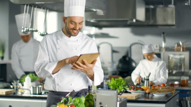 Famous Chef Uses Tablet Computer for Recipes While Working in a Modern Kitchen. His Help Work in the Background. video