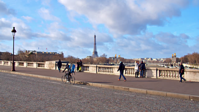 Famous Eiffel Tower Seen Across Distance From a Bridge in Paris. Cycler and Pedestrians