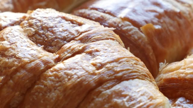 famous french croissant tasty dough rolls 4k 2160p 30fps ultrahd footage - viennoiserie buttery vienna-style pastry arranged on table 4k 3840x2160 uhd video - полумесяц форма предмета стоковые видео и кадры b-roll