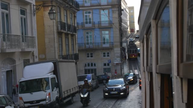 vídeos de stock e filmes b-roll de famous lisbon trams driving steep hills on narrow city streets - eletrico lisboa