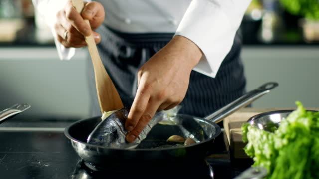 vídeos y material grabado en eventos de stock de famoso chef del restaurante voltea el pescado en un cacerola caliente. primer tiro de pan con verduras pintoresca vista. - pescado y mariscos