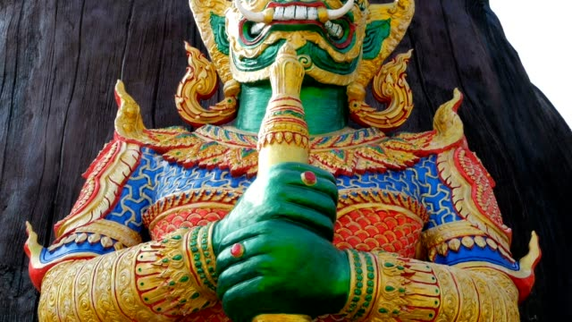 Famous Yaksha demon guardian statues A large statue of the mythological demon with a green face and white big fangs guards the entrance to the thai temple against the Buddha Gautama standing in the green and sunlight with the wheel of samsara. southeast stock videos & royalty-free footage