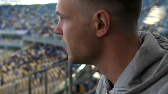 vídeos de stock e filmes b-roll de fan anxiously watching basketball match at stadium, commenting, team support - soccer supporter portrait