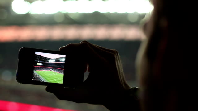 Fan Taking a Photo in the Sports Stadium / Arena Stock HD video clip footage of a man taking a photo in a Stadium floodlit stock videos & royalty-free footage