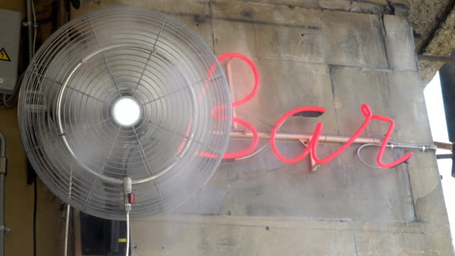 a fan with a water sprinkler cools the air on a hot day. - ritemprarsi video stock e b–roll