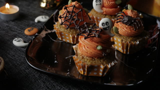 fancy halloween food party table with pumpkin cupcake muffin and cookies. - zucca video stock e b–roll