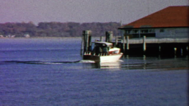 1967: Fancy powerboat docking on autumn lake boathouse. video