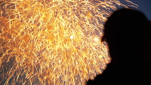 Fans of colorful explosion in the sky of the city watch firework close up 4K