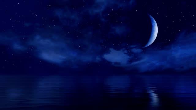 фантастическая большая половина луны в звездном ночном небе над спокойной поверхностью океана - полумесяц форма предмета стоковые видео и кадры b-roll