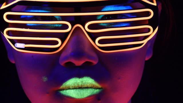 vídeos y material grabado en eventos de stock de fantástico video de sexy cyber raver mujer filmada en ropa fluorescente bajo luz negra ultravioleta. cyber chica brillan las mujeres raver en ropa fluorescente bajo luz negra ultravioleta, concepto del partido - color vibrante