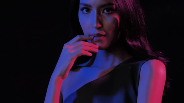 Fantastic video of sexy portrait of beautiful and sexy woman on black background under UV black light.Expressive facial expressions.Cosmetology and Spa.Beauty Face.Video: Diverse Portraits,Party concept