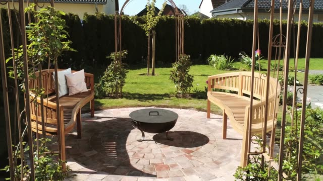 Fantastically beautiful garden with fire pit and rose arches lovingly designed garden ornamental garden stock videos & royalty-free footage