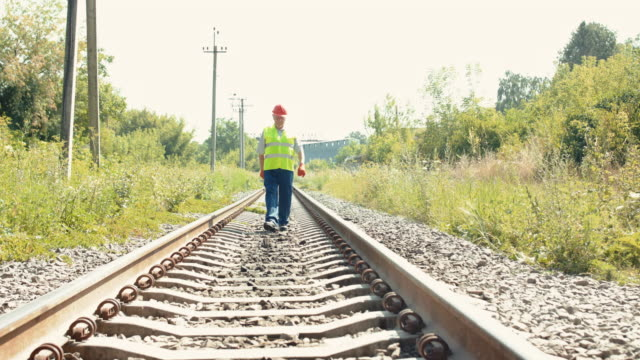 Far view of senior railroader in uniform walks on railway to camera with hammer video