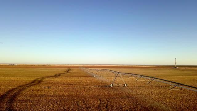 landwirtschaftliche bewässerung sprinklersystem und fracking-bohrgerät - bewässerungsanlage stock-videos und b-roll-filmmaterial