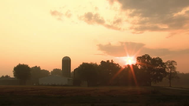 Farm Sunrise Time lapse of the sun rising over a farm. barns stock videos & royalty-free footage