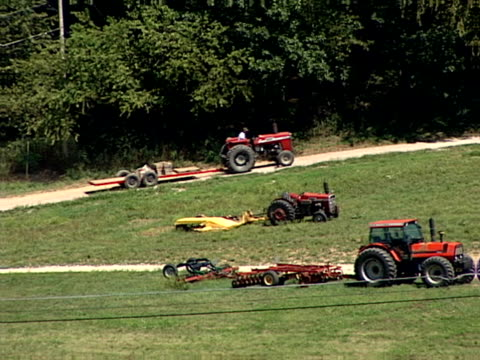 Farm Tractor A farmer rides his tractor up a hillside on his farm. agricultural occupation stock videos & royalty-free footage