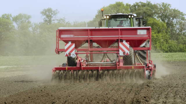 Farm tractor with trailer seeder sowing on plowed land. Cultivated field Farm tractor with trailer seeder sowing on plowed land. Sowing machine working on plowed field. Sowing process on agricultural field. Agricultural industry. Plowed field. Cultivated field harrow agricultural equipment stock videos & royalty-free footage