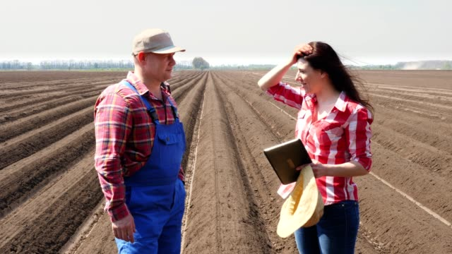 Farmer and agronomist stands between soil rows on field, with digital tablet, talking about quality of potatoe cultivator planting. shaking hands. modern agriculture. spring sunny day - vídeo