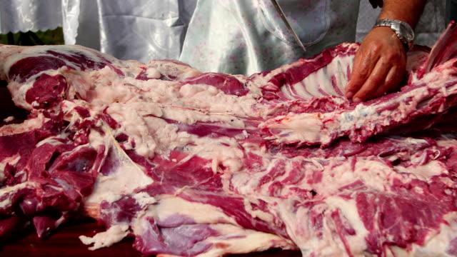 Farmer butchering a whole lamb, cutting lamb ribs and drying the meat Farmer butchering a whole lamb, cutting lamb ribs and drying the meat jerky stock videos & royalty-free footage
