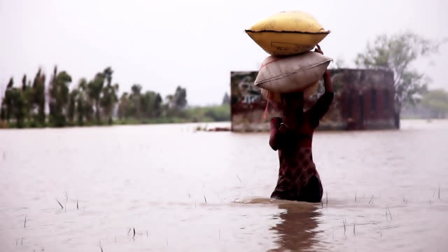 Farmer carrying sack on his head & walking video