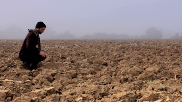 Farmer checks on poor soil. Long shot video