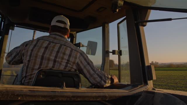 agricoltore coltivare campo - trattore video stock e b–roll