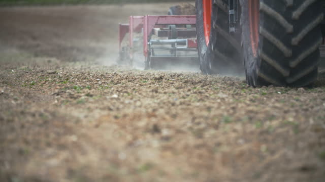 FARMING. Farmer cultivating field. Farmer is sowing and cultivating field in summer at dawn. Close up of harrows plowing field. sowing stock videos & royalty-free footage