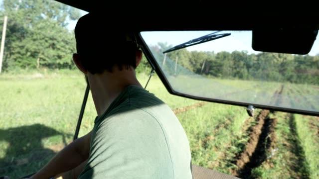Farmer driving tractor on the potato field in potato harvesting process video