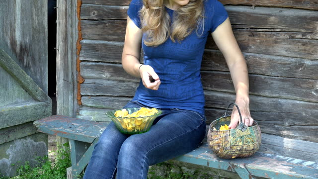Farmer girl hands clean chanterelle mushrooms with knife video