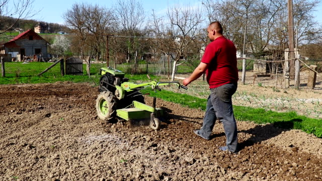 Farmer in a mini tractor plowing the field - Stock video Hand tractor cultivator, Agricultural Machinery, Agriculture, Cultivated harrow agricultural equipment stock videos & royalty-free footage
