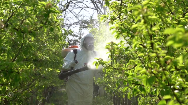 farmer in coveralls with gas mask spraying orchard with atomizer sprayer in slow motion - insetticida video stock e b–roll