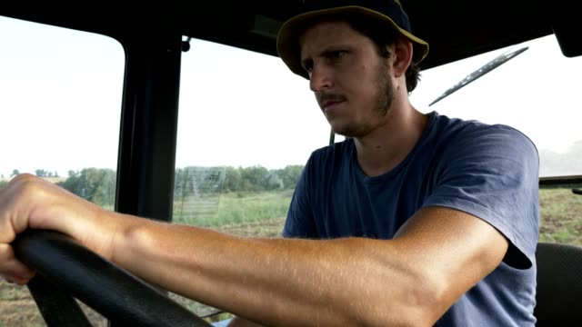 Farmer in hat, sits inside in the tractor cabin, rides on the field with plow. Portrait of young farmer in hat, sits inside in the tractor cabin, rides on the field. Real plowing process at organic eco farm. harrow agricultural equipment stock videos & royalty-free footage