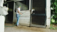 istock A Farmer in His Seventies Fills up the Water Bucket with a Hose in a Horse Stall in a Barn on a Farm and Walks Away 1215997838