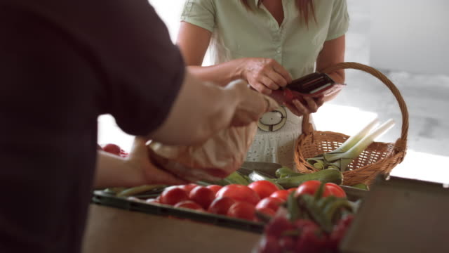 Farmer in the marketplace handing produce to female customer video