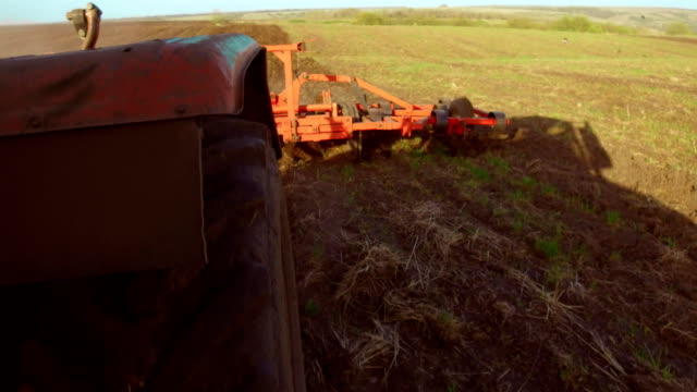 Farmer in tractor plows Russia steadicam motion agriculture soil the ground preparing land with seedbed cultivator as part of pre seeding activities in early spring season lifestyle of agricultural works at farmlands. agriculture concept - vídeo